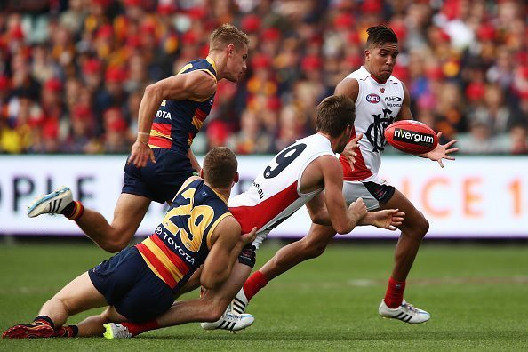 ADELAIDE, AUSTRALIA - APRIL 18: Ben Newton of the Demons passes the ball to Jay Kennedy-Harris of the Demons during the round three AFL match between the Adelaide Crows and the North Melbourne Kangaroos at Adelaide Oval on April 18, 2015 in Adelaide, Australia. (Photo by Morne de Klerk/Getty Images)