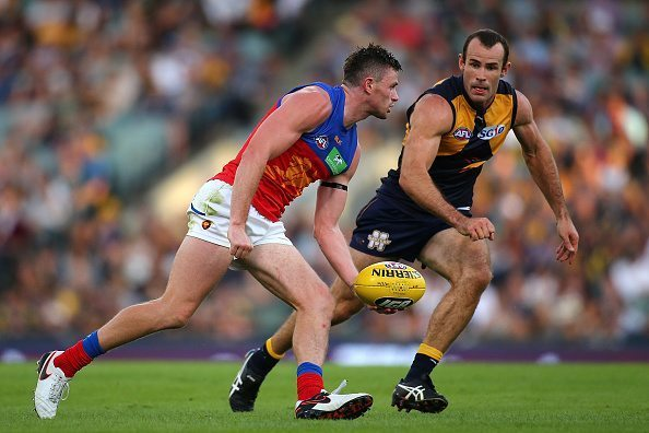 PERTH, WESTERN AUSTRALIA - MARCH 27: Pearce Hanley of the Lions looks to handball against Shannon Hurn of the Eagles during the AFL round one match between the West Coast Eagles and the Brisbane Lions at Domain Stadium on March 27, 2016 in Perth, Australia. (Photo by Paul Kane/Getty Images)