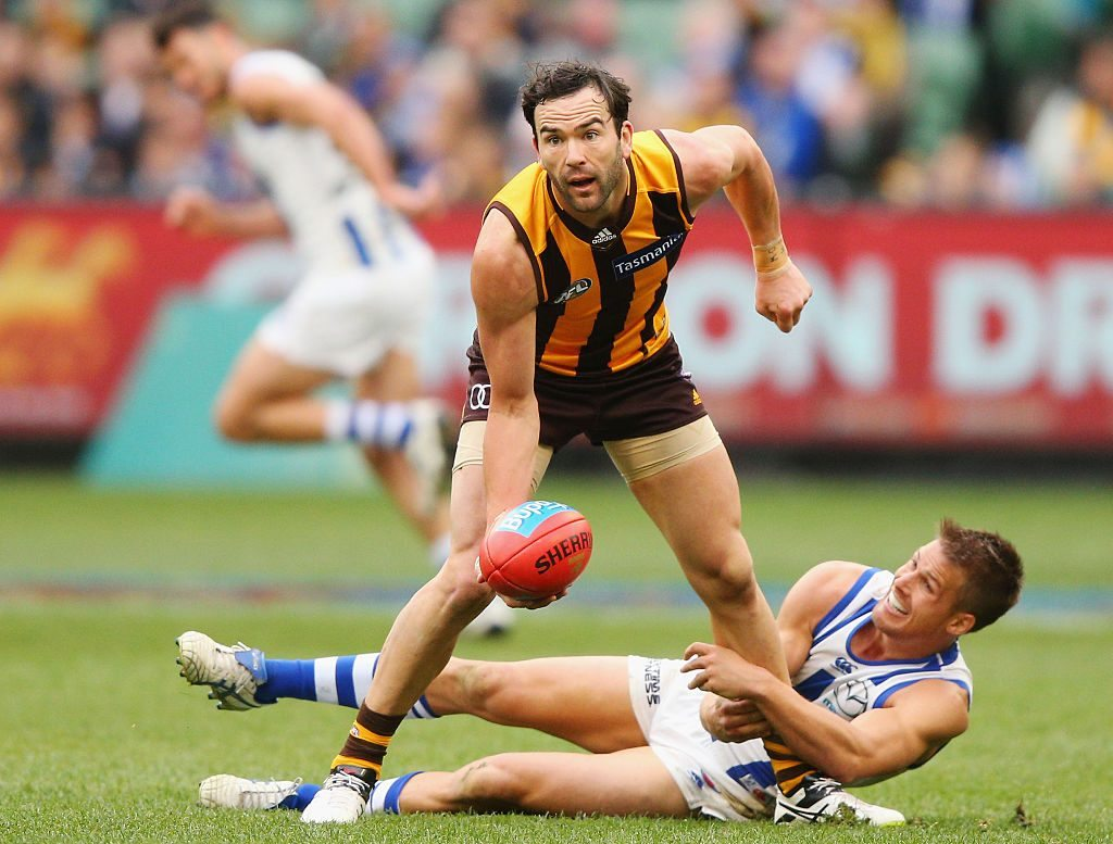 MELBOURNE, AUSTRALIA - AUGUST 13: Jordan Lewis of the Hawks handballs away from Andrew Swallow of the Kangaroos during the round 21 AFL match between the Hawthorn Hawks and the North Melbourne Kangaroos at Melbourne Cricket Ground on August 13, 2016 in Melbourne, Australia. (Photo by Michael Dodge/Getty Images)